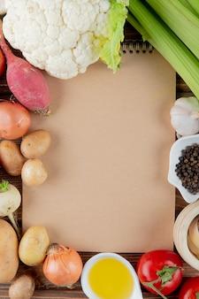 Vista superiore delle verdure come sedano e altri del pomodoro del ravanello del cavolfiore con burro e pepe nero con lo spazio della copia
