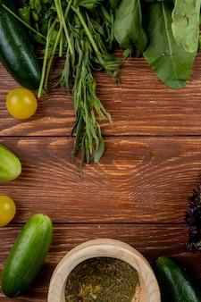 Vista superiore delle verdure come spinaci alla menta del pomodoro del cetriolo con pepe nero su legno