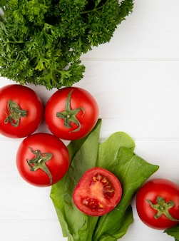 Vista superiore delle verdure come spinaci del pomodoro di coriandolo su superficie di legno