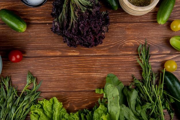 Vista superiore delle verdure come spinaci della lattuga alla menta del basilico del pomodoro del cetriolo con il sale del pepe nero su legno