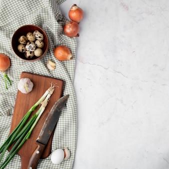 Vista superiore delle verdure come uovo della cipolla dell'aglio sul panno su fondo bianco con lo spazio della copia