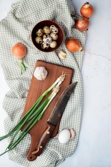 Vista superiore delle verdure come uovo di aglio della cipolla con il coltello sul tagliere sul panno su fondo bianco