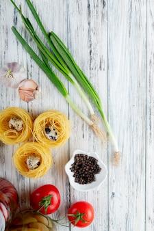 Vista superiore delle verdure come uovo di pomodoro dell'aglio dello scalogno con pepe nero e vermicelli su fondo di legno con lo spazio della copia