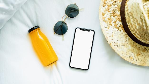 Vista superiore dello schermo vuoto di smartphone in camera e cappello, occhiali, durante il tempo libero.