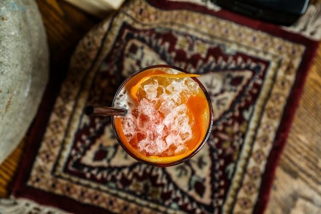 Vista superiore dello scintillio dell'acqua frizzante del ghiaccio arancio dei peals del cocktail arancio
