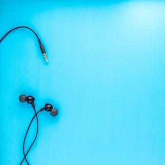Vista superiore di auricolari neri su sfondo blu