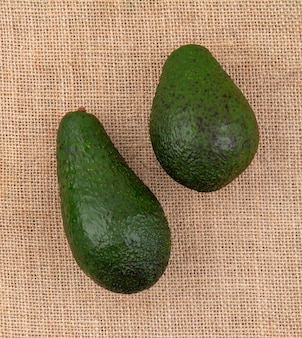 Vista superiore di avocado sani freschi verdi sulla superficie del panno di sacco