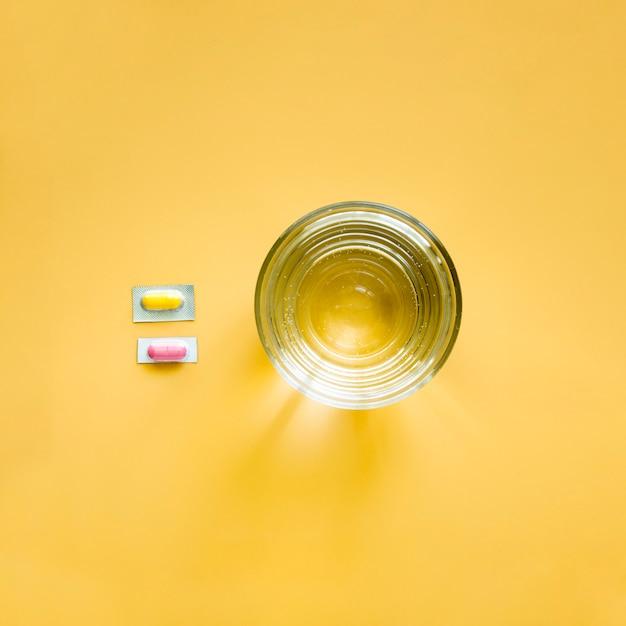Vista superiore di bicchiere d'acqua e pillole in un foglio