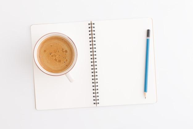 Vista superiore di caffè e matita e taccuino su priorità bassa bianca