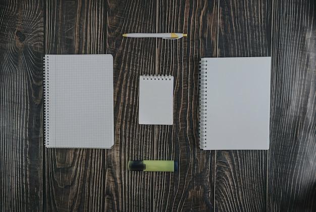 Vista superiore di carta per appunti in bianco con la penna e l'indicatore sulla tavola di legno marrone per fondo