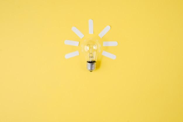 Vista superiore di concetto piano laico creativo della lampadina sul fondo della carta di colore giallo.