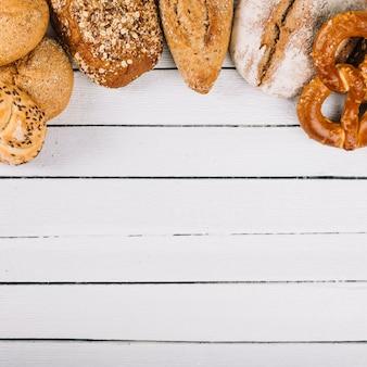 Vista superiore di delizioso pane appena sfornato su fondo di legno