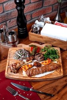 Vista superiore di diversi tipi di kebab witj cipolla ed erbe su una tavola di legno