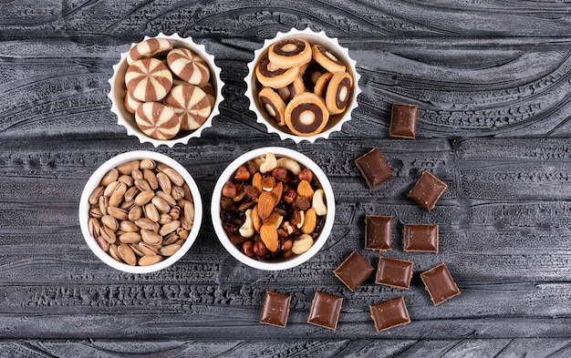 Vista superiore di diversi tipi di snack come noci, biscotti e cioccolato in ciotole su superficie scura orizzontale