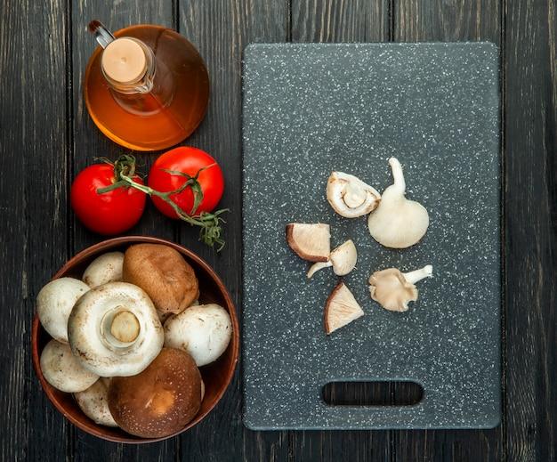 Vista superiore di funghi freschi in una ciotola di legno bottiglia di olio d'oliva e pomodori freschi affettati funghi sul tagliere nero su fondo nero