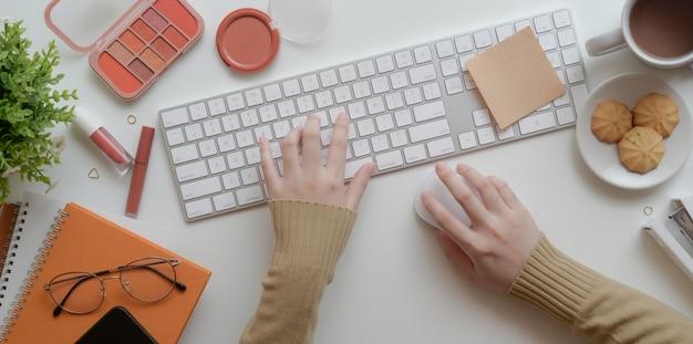 Vista superiore di giovane battitura a macchina femminile sulla tastiera nel concetto femminile beige caldo dell'area di lavoro