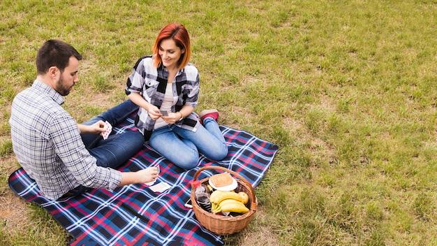 Vista superiore di giovani coppie sorridenti che giocano con le carte sulla coperta al picnic