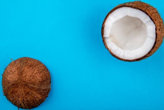 Vista superiore di grande noce di cocco fresca divisa in due sulla superficie del blu