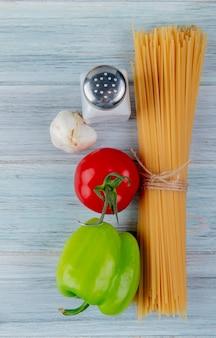 Vista superiore di maccheroni di vermicelli con aglio e sale del pepe del pomodoro su superficie di legno