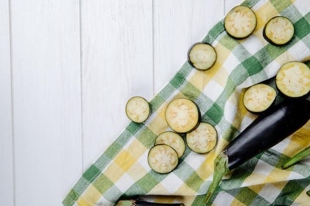 Vista superiore di melanzane fresche con le fette tagliate sul tessuto del plaid su rustico bianco con lo spazio della copia