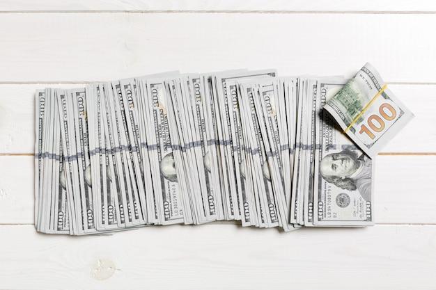 Vista superiore di mentire 100 banconote in dollari in una riga su fondo di legno