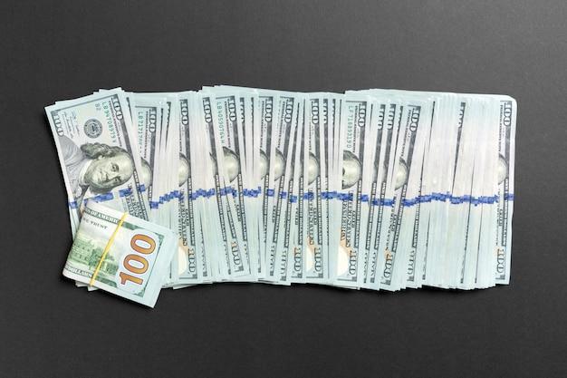 Vista superiore di mentire 100 banconote in dollari in una riga su sfondo colorato. chiuda in su del concetto di risparmio di denaro