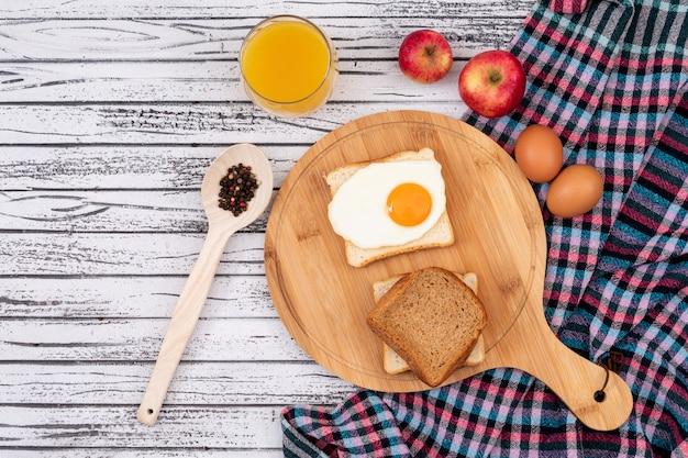 Vista superiore di pane tostato con l'uovo e il succo sull'orizzontale di superficie di legno bianco