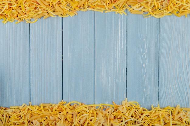 Vista superiore di pasta cruda di diverse forme e tipi con spazio di copia su fondo rustico in legno