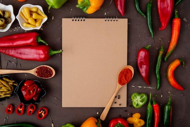 Vista superiore di peperoni e spezie e peperoni salati con il blocco note su fondo marrone rossiccio con lo spazio della copia
