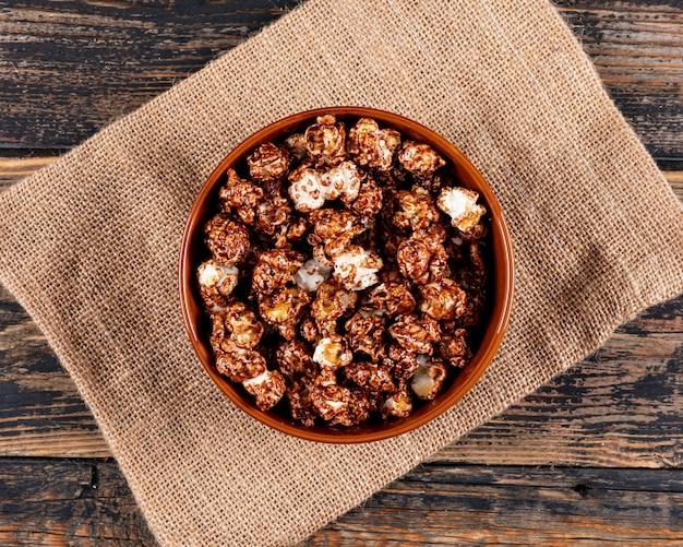 Vista superiore di popcorn in ciotola e tela di sacco su orizzontale di legno scuro