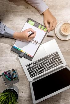 Vista superiore di scrittura dell'uomo d'affari in blocco note con il computer portatile, il caffè, la pianta in vaso e gli accessori di affari