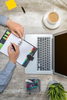 Vista superiore di scrittura dell'uomo d'affari in taccuino con il computer portatile, il caffè, le note appiccicose, la pianta in vaso e gli accessori di affari