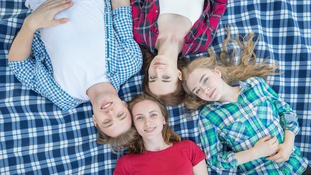 Vista superiore di studenti che si trovano sulla coperta da picnic