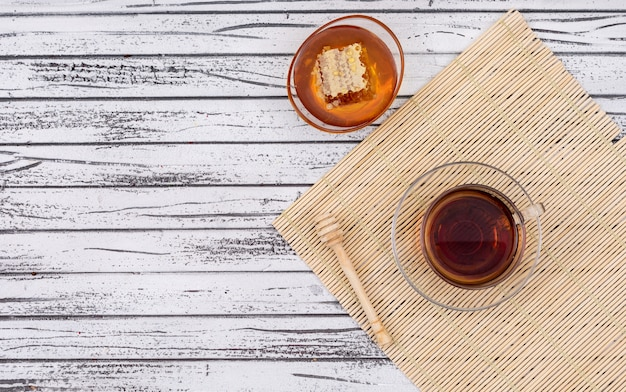 Vista superiore di tè con miele e lo spazio della copia sull'orizzontale di legno bianco del fondo