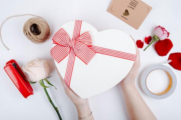 Vista superiore di un contenitore di regalo a forma di cuore con un arco e una rosa e una cucitrice meccanica bianche di colore con la corda e la cartolina su fondo bianco