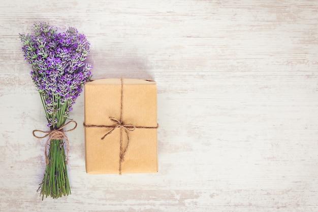 Vista superiore di un contenitore di regalo avvolto in carta kraft e bouquet di lavanda su fondo rustico di legno bianco