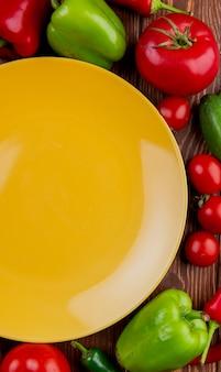 Vista superiore di un piatto giallo vuoto e dei pomodori e dei cetrioli variopinti dei peperoni dolci degli ortaggi freschi su legno rustico