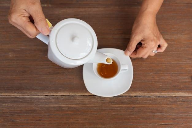 Vista superiore di un tè di versamento femminile sulla tavola di legno