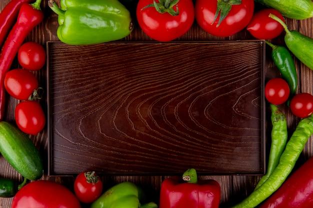Vista superiore di un vassoio di legno vuoto e dei pomodori maturi degli ortaggi freschi peperoncini verdi e rossi e peperoni variopinti su rustico