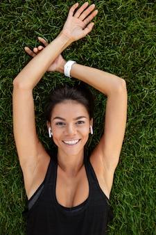 Vista superiore di una donna felice di forma fisica nella stenditura delle cuffie