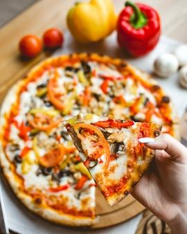 Vista superiore di una mano femminile che tiene un pezzo di pizza con i pomodori e il formaggio dei peperoni dolci dei funghi sul fondo di legno della tavola