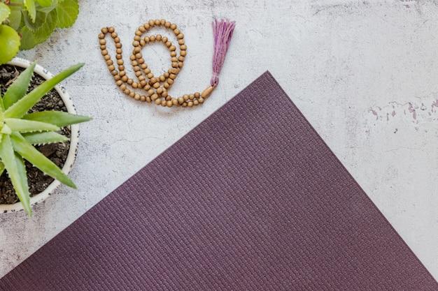 Vista superiore di una stuoia viola di yoga, cattive perle di legno su fondo bianco. accessori essenziali per praticare yoga e meditazione. copia spazio