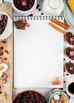Vista superiore di uno sketchbook e chicchi di caffè in ciotola di legno e cucchiai su fondo rustico