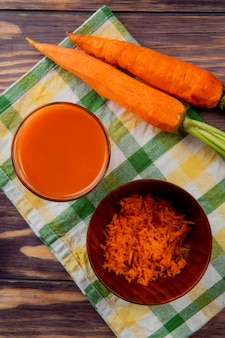 Vista superiore di vetro del succo di carota con la ciotola di carota grattugiata e le intere carote sul panno su fondo di legno