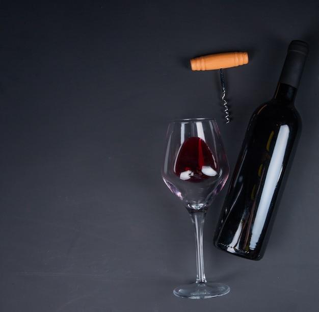 Vista superiore di vino rosso in vetro e bottiglia distesi con la cavaturaccioli sul nero con lo spazio della copia