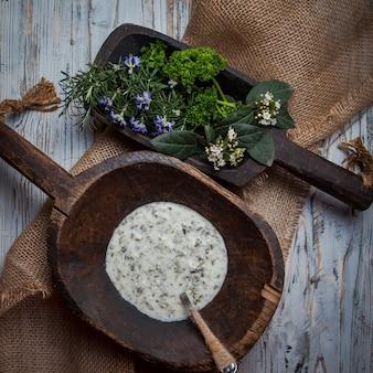 Vista superiore dovga con foglie di rosmarino e cucchiaio nel piatto di legno