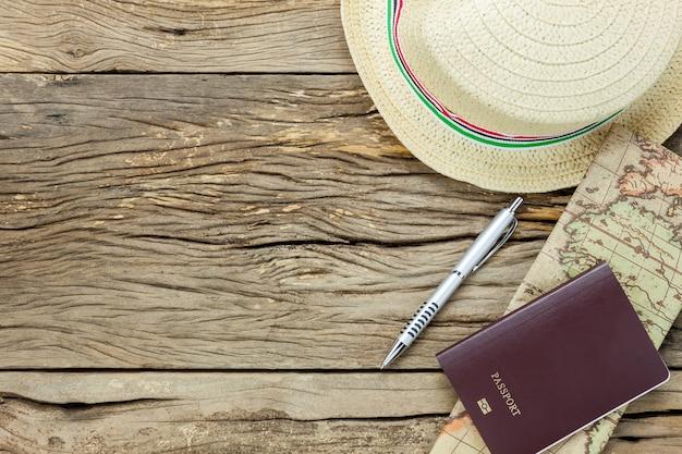 Vista superiore elementi essenziali da percorrere. la carta passaporto cappello da penna su sfondo rustico di legno.
