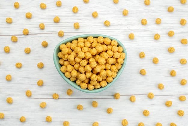 Vista superiore giallo crudo dei cereali colorato dentro il piatto blu su bianco, salute dei fiocchi di granturco della prima colazione del cereale