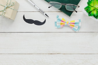 Vista superiore Happy Father day.accessories con albero, baffi, cravatta d'arco vintage, presente, penna, libro di nota e occhiali su sfondo rustico in legno bianco.