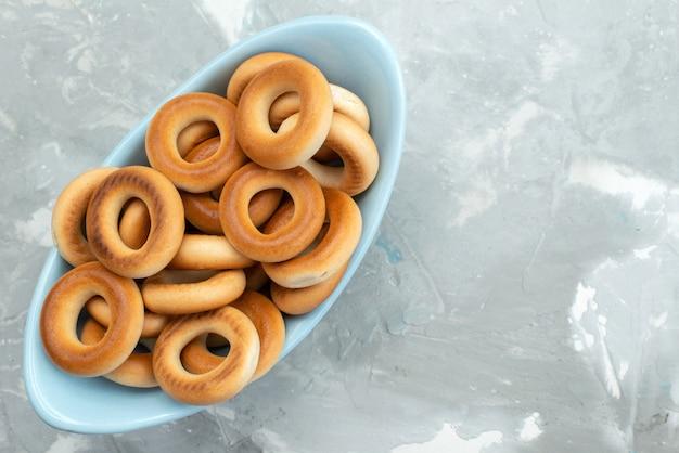 Vista superiore intorno ai cracker dolci dentro il piatto blu sullo spuntino bianco e croccante delle patatine fritte